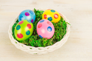 Easter basket with four colorful dotted Easter eggs