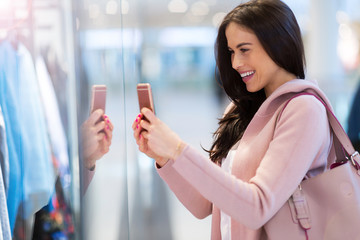 Woman using mobile phone in shopping mall