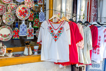 Ethnic shirts with traditional Hungarian embroidery and decorative painted plates and cutting boards in a street store