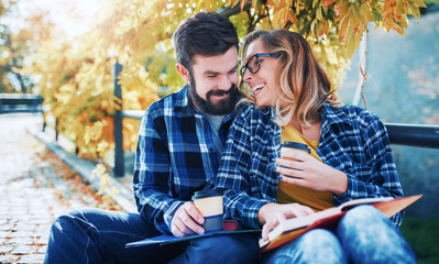 Couple of students with a books in the park. Education, love and tenderness, dating, romance, lifestyle concept