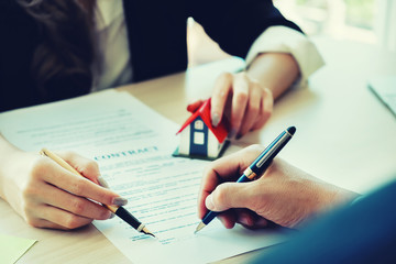 Contract paper,estate agent gives pen and documents agreement with customer to sign contract.