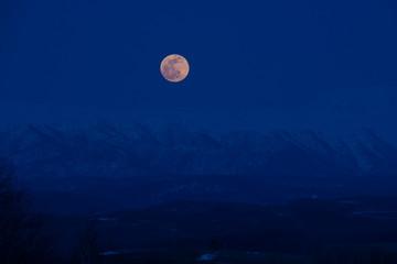残雪の山並みから上る満月 十勝岳連峰