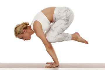 Yoga, sport, training and lifestyle concept - Young blonde woman in white sportswear doing yoga practice.Crane pose ,bakasana