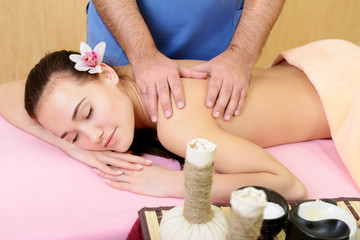 Body care. Beautiful young woman relaxing with hand massage at beauty spa salon. Back manual massage.