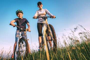 Mother and start to ride a bicykles