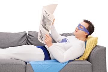 Superhero lying on a sofa and reading a newspaper