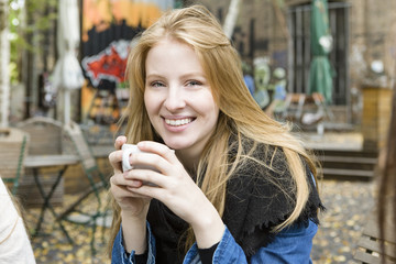Germany, Berlin, Portrait of a teenage girl drinking coffee at outdoor cafe