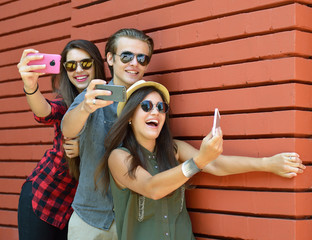 Young people having fun outdoor and making selfie with smart phone against red brick wall. Urban lifestyle, happiness, joy, friends, lelf photo social network concept. Image toned and noise added.