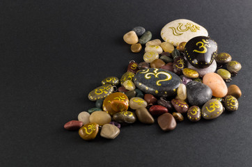 Pile of little decorative stones painted with Om symbol