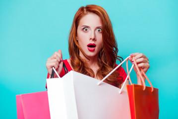 Young beautfiul redhead girl with shopping bags