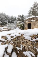 mur en pierres sèches et capitelle sous la neige
