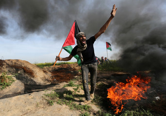 A demonstrator holds a Palestinian flag as he shouts during clashes with Israeli troops, near the border with Israel in the southern Gaza Strip
