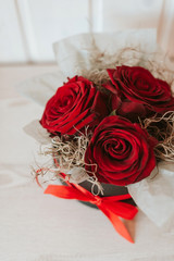 Romantic luxury red roses in a black gift box with red ribbon.
