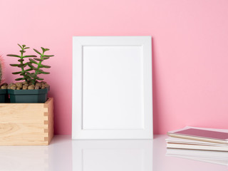 Blank white frame and plant cactus on a white table against the pink wall with copy space. Mockup with copy space.