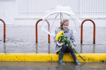 little girl sitting in the street with a bouquet of flowers in rain day and  umbrella