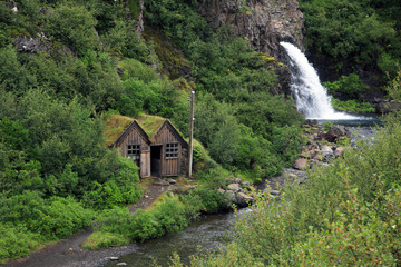 Old barns near the small waterfall in Iceland
