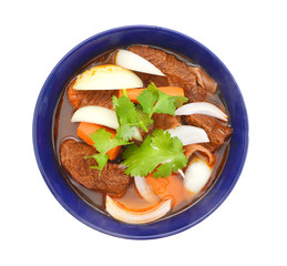 beef stew and vegetables in blue bowl on white background