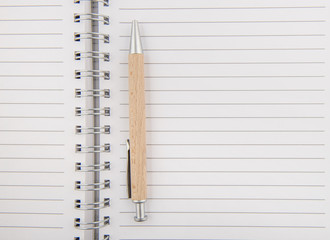 Opened notepad with wooden pen
