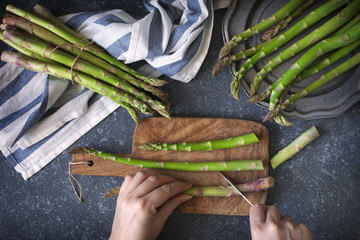 Fresh  raw asparagus on stone background. Women female hands cut asparagus on wooden cooking board. Top view