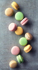 Colorful macarons on gray marble background