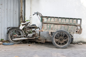Old broken motorbike - tricycle parked in the street, Ho Chi Minch City, Vietnam.