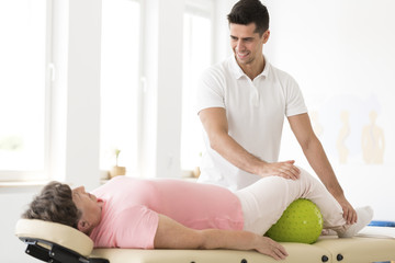 Physiotherapist supporting senior woman