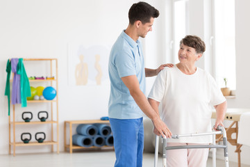 Elderly woman and caring physiotherapist