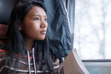The young woman looks from window and reads a book on a train. Beautiful asian girl in sweater goes on a train with a book.