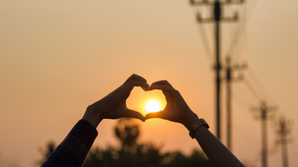 The hands of men and women made heart shaped, with the sun in the middle.