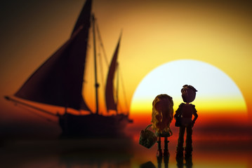 A boy with a girl at sunset escorted sailboat.