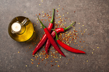 Red chili pepper and pitcher of oil on stone background