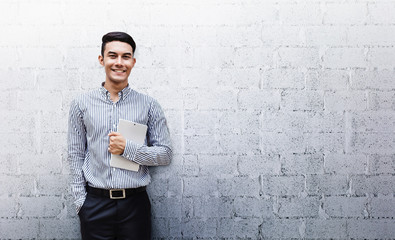 Happy Friendly Young Businessman standing at the Wall, Smile and holding a Digital Tablet, Lifestyle of modern male. Looking at camera