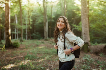 Pretty young woman smiling happy carrying backpack in the forest on sunset light in the autumn season.
