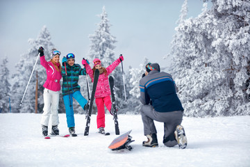 father taking picture of family on snow.outdoor in sunny day.