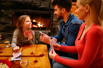 cute girl playing card game with parents