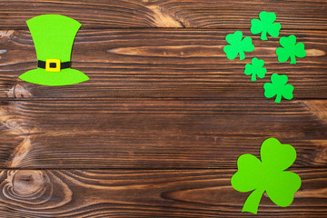 St. Patrick's Day theme colorful horizontal banner. Green leprechaun hat and shamrock leaves on brown wooden background. Felt craft elements. Copy space. For greeting card,congratulation banner