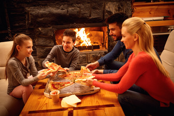 Smiling parents and children eating pizza together