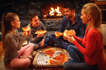 Smiling parents and children eating pizza on the floor