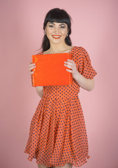 Attractive woman with makeup holds red box or gift.