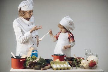 Mother teaches son to cook on light background