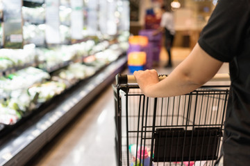 Close up shopper wifehouse woman's hand is pushing a shopping cart at supermarket, retail, supermart, store or groceries aisle. Have copy space on left hand side.