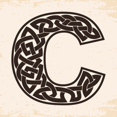 Letter of the English alphabet with Celtic national ornament as interlaced ribbon on a beige background. Paryrus with the aging effect.
