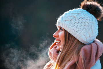 Smiling woman wearing knitted woolen cap and big scarf at cold winter day
