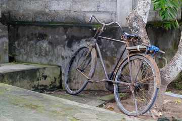 Parked old bicycle near stone wall in Asia.