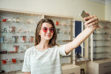 You think I should buy glasses or not. Portrait of glamourous attractive woman on shopping standing in optician store, taking selfie in trendy sunglasses and smiling, choosing what frame suit her most
