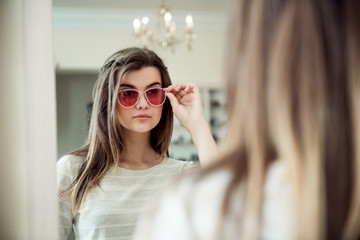 Attractive woman on hunt for new trendy things. Indoor portrait of stylish young caucasian woman in optician store trying on fashionable sunglasses while standing near mirror, picking from variants