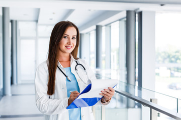 Beautiful happy female doctor with paperboard