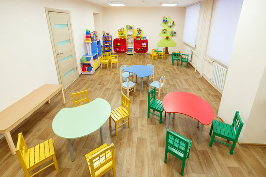 Spacious light pink colored game room with tables for classes in the kindergarten