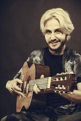 Blonde man playing acoustic guitar