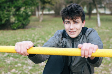 A boy of adolescence is engaged in sports on a sports ground. He smiles and his braces are clearly visible on his teeth